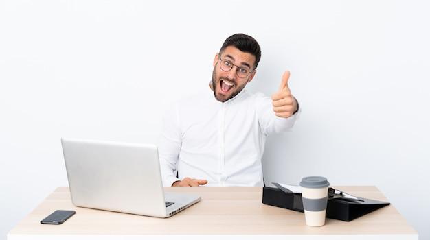 Młody biznesmen w miejscu pracy z kciukami do góry, ponieważ stało się coś dobrego