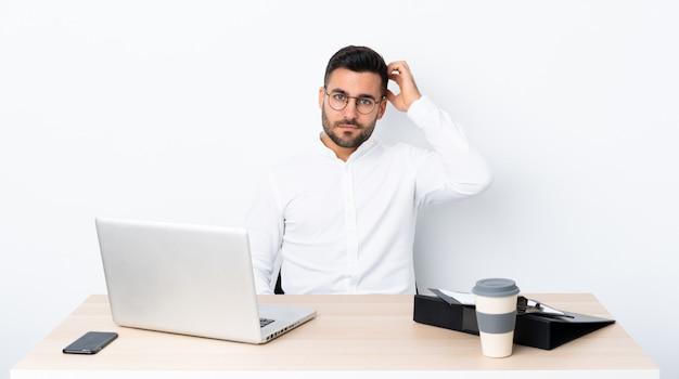 Młody biznesmen w miejscu pracy z wyrazem frustracji i braku zrozumienia