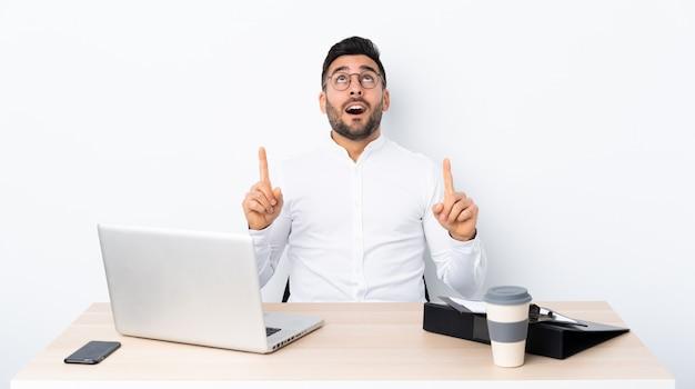 Młody biznesmen w miejscu pracy zaskakujący i wskazuje up
