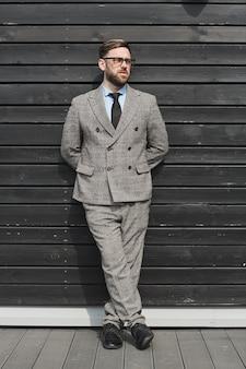 Młody biznesmen w okularach iw garniturze, opierając się na ścianie w mieście i odwracając wzrok z zamyśleniem
