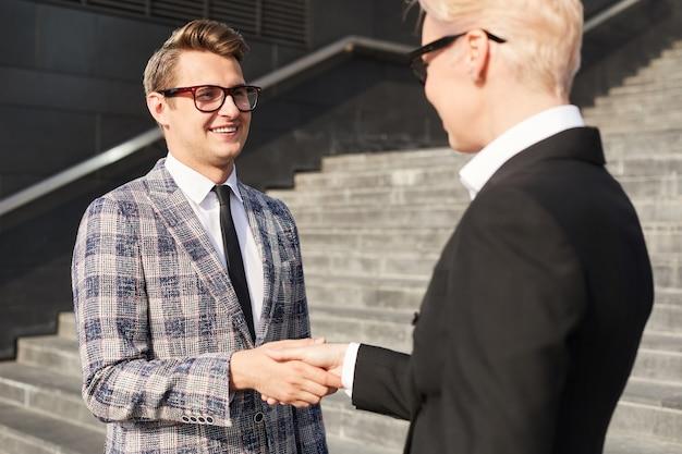 Młody biznesmen w okularach, ściskając ręce do interesu stojącego na schodach na zewnątrz