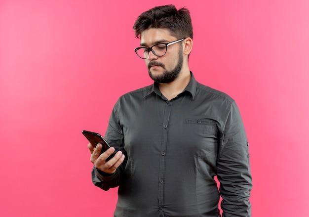 Młody biznesmen w okularach, trzymając i patrząc na telefon na różowym tle