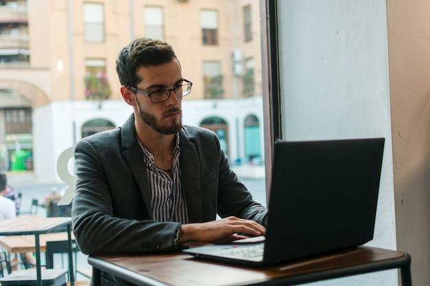 Młody biznesmen w pubie pracuje z jego laptopem