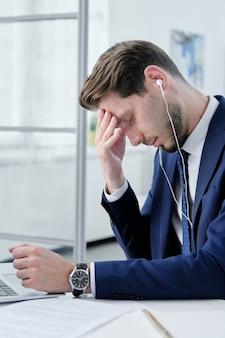 Młody biznesmen w słuchawkach zmęczony pracą biurową siedzi przy biurku i pocieranie czoła czując ból głowy