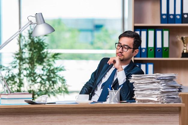 Młody biznesmen w stresie z dużą ilością papierkowej roboty