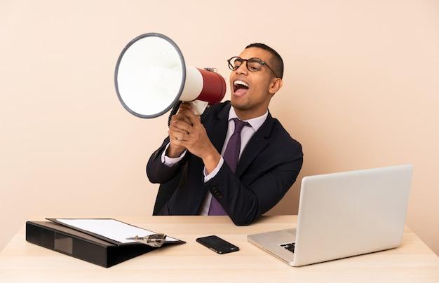 Młody biznesmen w swoim biurze z laptopem i innymi dokumentami krzyczy przez megafon