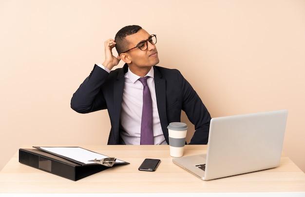 Młody biznesmen w swoim biurze z laptopem i innymi dokumentami mającymi wątpliwości podczas drapania głowy