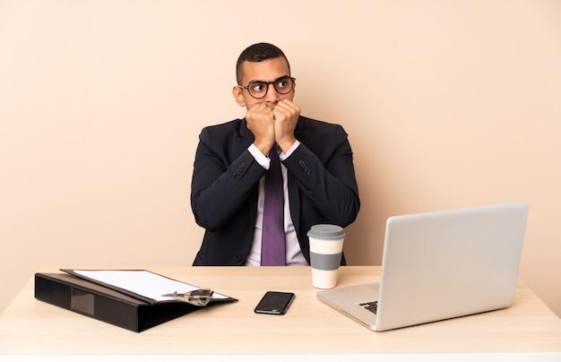 Młody biznesmen w swoim biurze z laptopem i innymi dokumentami, nerwowy i przestraszony, wkładając ręce do buzi