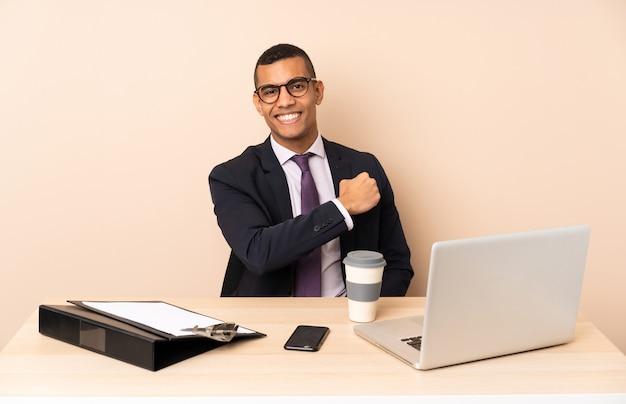 Młody biznesmen w swoim biurze z laptopem i innymi dokumentami świętuje zwycięstwo