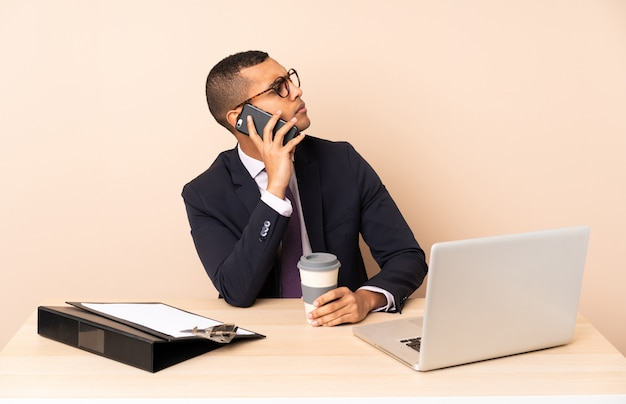 Młody biznesmen w swoim biurze z laptopem i innymi dokumentami trzyma kawę na wynos i telefon komórkowy