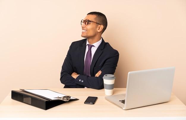 Młody biznesmen w swoim biurze z laptopem i innymi dokumentami w pozycji bocznej