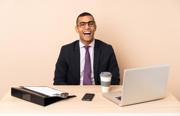 Młody biznesmen w swoim biurze z laptopem i innymi dokumentami z niespodzianką wyraz twarzy