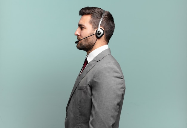 Młody biznesmen w widoku profilu, który chce skopiować przestrzeń do przodu, myśląc, wyobrażając sobie lub marząc o koncepcji telemarketingu