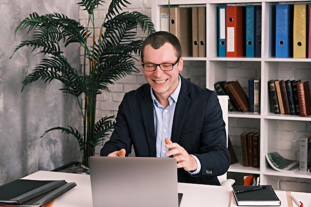 Młody biznesmen wesoły człowiek w okularach za pomocą laptopa siedzi w biurze przy stole na sobie garnitur, uśmiecha się, patrząc do laptopa