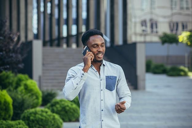 Młody biznesmen, wesoły rozmawiający przez telefon komórkowy w zwykłych ubraniach, wolny strzelec szczęśliwie komunikuje się z kolegami