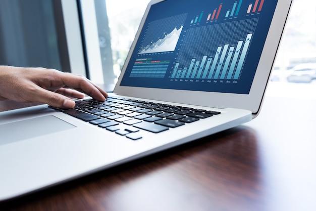 Młody biznesmen wielozadaniowość za pomocą laptopa