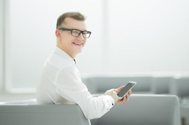 Młody biznesmen wpisując sms na swoim smartfonie. ludzie i technologia