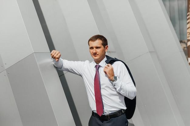 Młody biznesmen wraca do domu z pracy, niosąc kurtkę na ramieniu, uśmiechając się, pozując w pobliżu biurowca