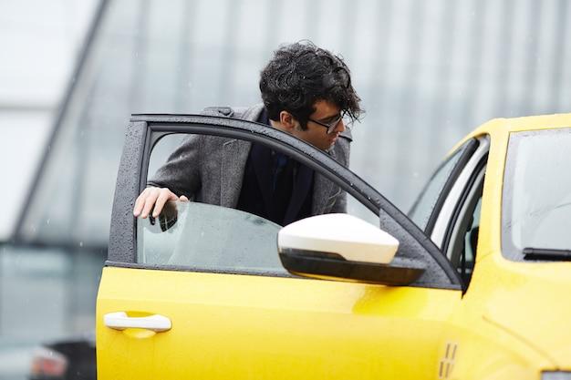 Młody biznesmen wsiada do taksówki