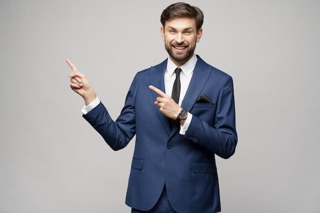 Młody biznesmen, wskazując na copyspace palcem