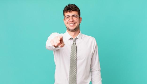 Młody biznesmen wskazujący na aparat z zadowolonym, pewnym siebie, przyjaznym uśmiechem, wybierający ciebie