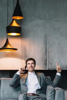 Młody biznesmen wskazuje jego palec oddolny podczas gdy opowiadający na telefonie komórkowym