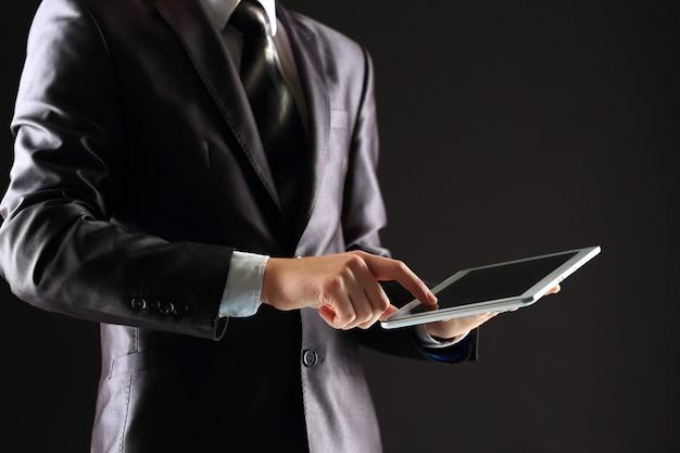 Młody biznesmen współpracuje z nowoczesnymi urządzeniami, cyfrowym komputerem typu tablet i telefonem komórkowym.