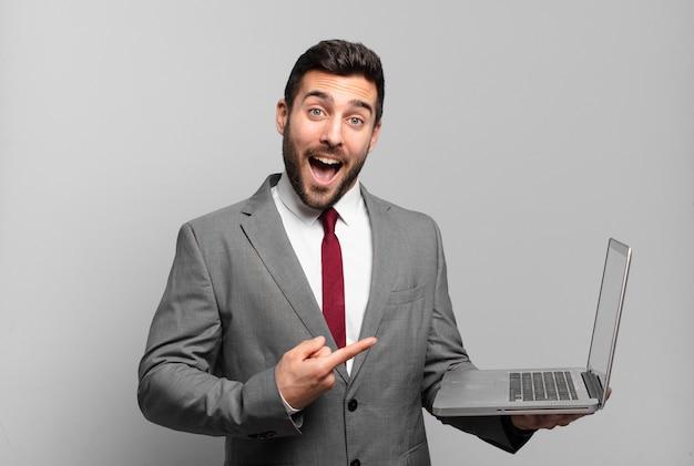 Młody biznesmen wygląda na podekscytowanego i zaskoczonego, wskazując na bok i w górę, aby skopiować przestrzeń i trzymając laptopa