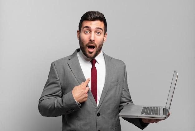 Młody biznesmen wygląda na zszokowanego i zdziwionego z szeroko otwartymi ustami, wskazując na siebie i trzymając laptopa