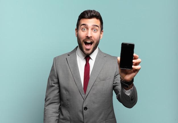 """Młody biznesmen wyglądający na bardzo zszokowanego lub zaskoczonego, gapiący się z otwartymi ustami, mówiący """"wow"""" i pokazujący ekran swojego telefonu"""
