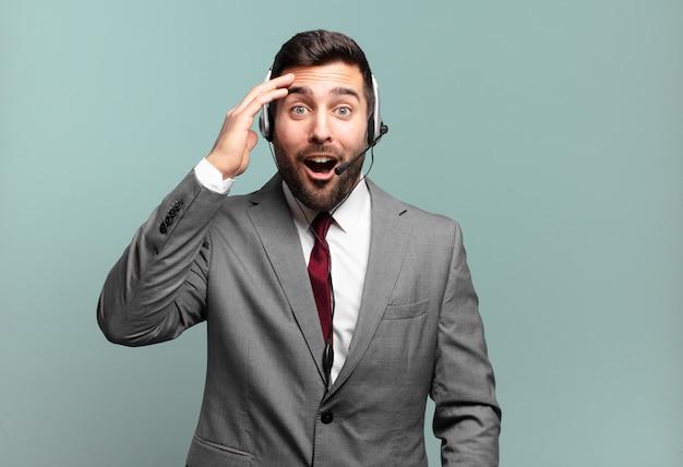 Młody biznesmen wyglądający na szczęśliwego, zdziwionego i zdziwionego, uśmiechnięty i realizujący niesamowitą i niesamowitą koncepcję telemarketingu z dobrymi wiadomościami