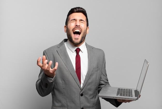 Młody biznesmen wyglądający na zdesperowanego i sfrustrowanego, zestresowanego, nieszczęśliwego i zirytowanego, krzyczy i krzyczy i trzyma laptopa