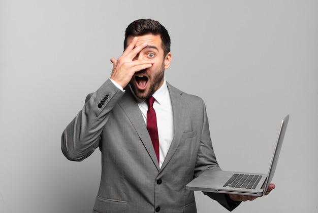 Młody biznesmen wyglądający na zszokowanego, przestraszonego lub przerażonego, zakrywający twarz dłonią i zerkający między palcami i trzymający laptopa