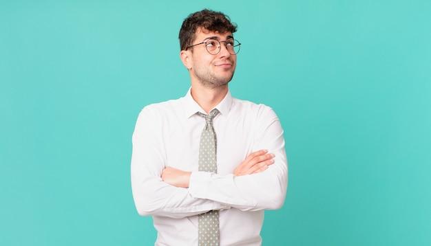 Młody biznesmen wzrusza ramionami, czuje się zdezorientowany i niepewny, wątpi ze skrzyżowanymi rękoma i patrzy na zdziwienie