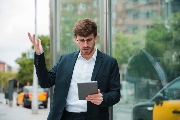 Młody biznesmen wzrusza ramionami podczas gdy patrzejący cyfrową pastylkę