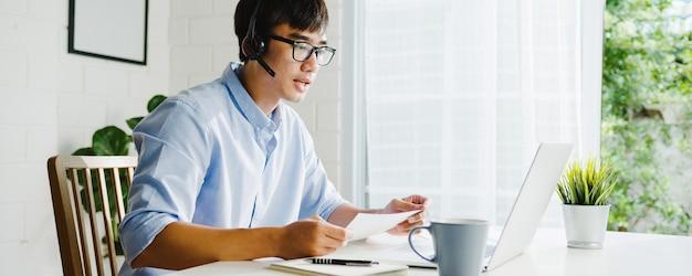 Młody biznesmen z azji za pomocą laptopa rozmawia ze współpracownikami o planie w rozmowie wideo, podczas gdy inteligentna praca w domu w salonie. samoizolacja, dystans społeczny, kwarantanna w celu zapobiegania koronawirusom.