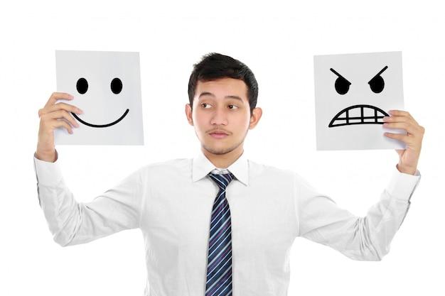 Młody biznesmen z gniewnymi i szczęśliwymi twarzami na papierze