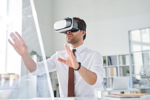 Młody biznesmen z goglami vr oglądając prezentację lub wchodząc w interakcję w wirtualnej rzeczywistości