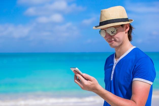 Młody biznesmen z jego telefonem na plaża wakacje