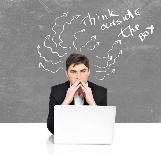 Młody biznesmen z laptopa burzy mózgów.