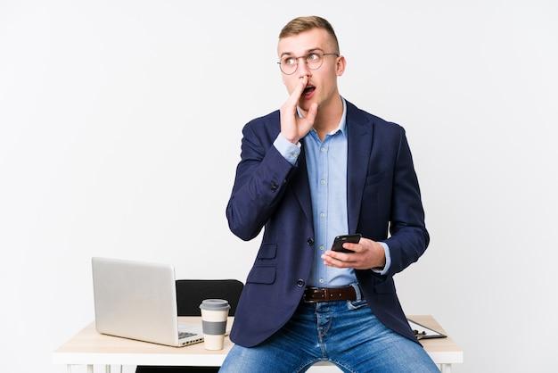 Młody biznesmen z laptopem mówi tajne gorące hamowanie wiadomości i patrzy na bok