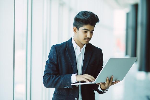 Młody biznesmen z laptopem pracuje przy biurem