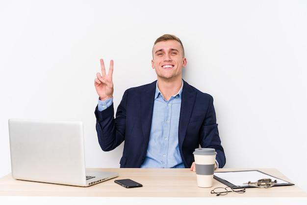 Młody biznesmen z laptopem radosny i beztroski, pokazując symbol pokoju palcami.