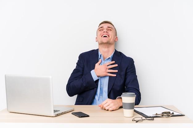 Młody biznesmen z laptopem śmieje się głośno, trzymając rękę na piersi.