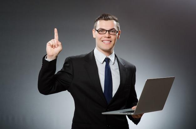 Młody biznesmen z laptopem w biznesowym pojęciu