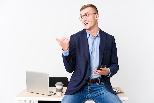 Młody biznesmen z laptopem wskazuje kciukiem palca, śmiejąc się i beztroski.