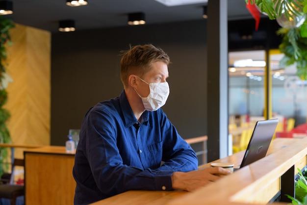Młody biznesmen z maską myśli i siedzi z odległością wewnątrz kawiarni