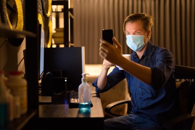 Młody biznesmen z maską trzymając kawę i biorąc selfie podczas pracy w domu późno w nocy