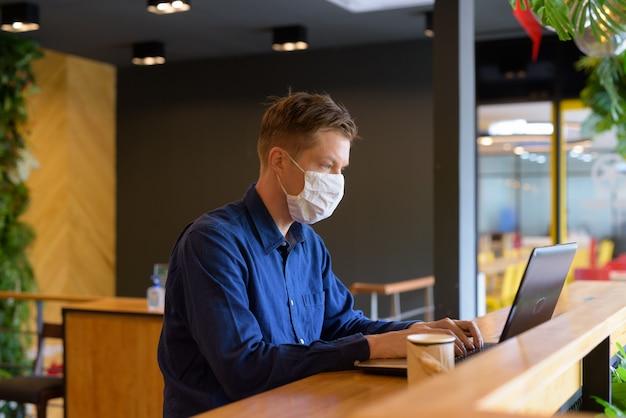 Młody biznesmen z maską za pomocą laptopa i siedząc z odległością wewnątrz kawiarni