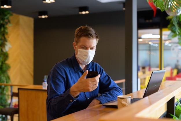 Młody biznesmen z maską za pomocą telefonu i siedząc z odległością wewnątrz kawiarni